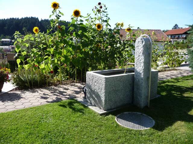 Brunnen vor dem Haus Hienhartweg 11 mit Sonnenblumen